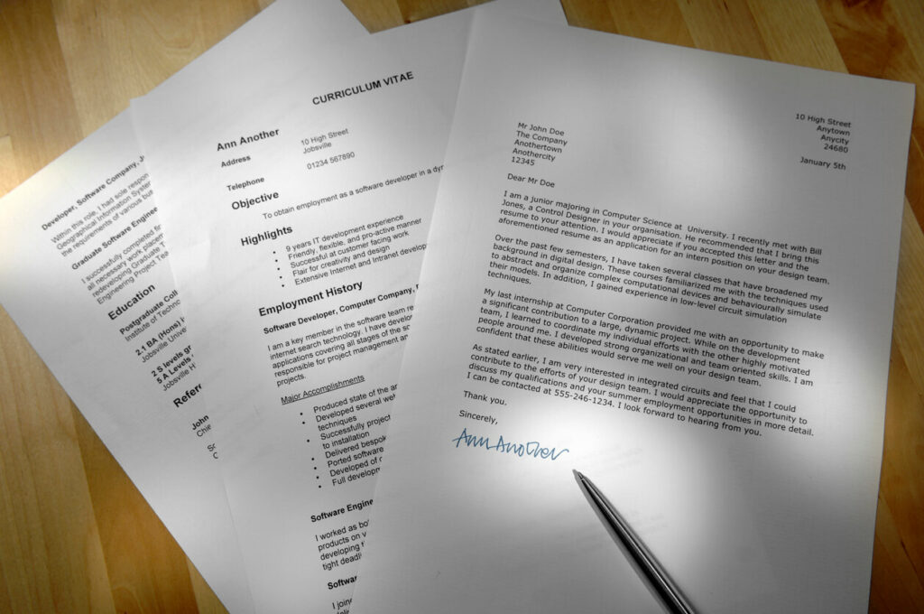 Job application documents on a table, showing a cover letter and resume