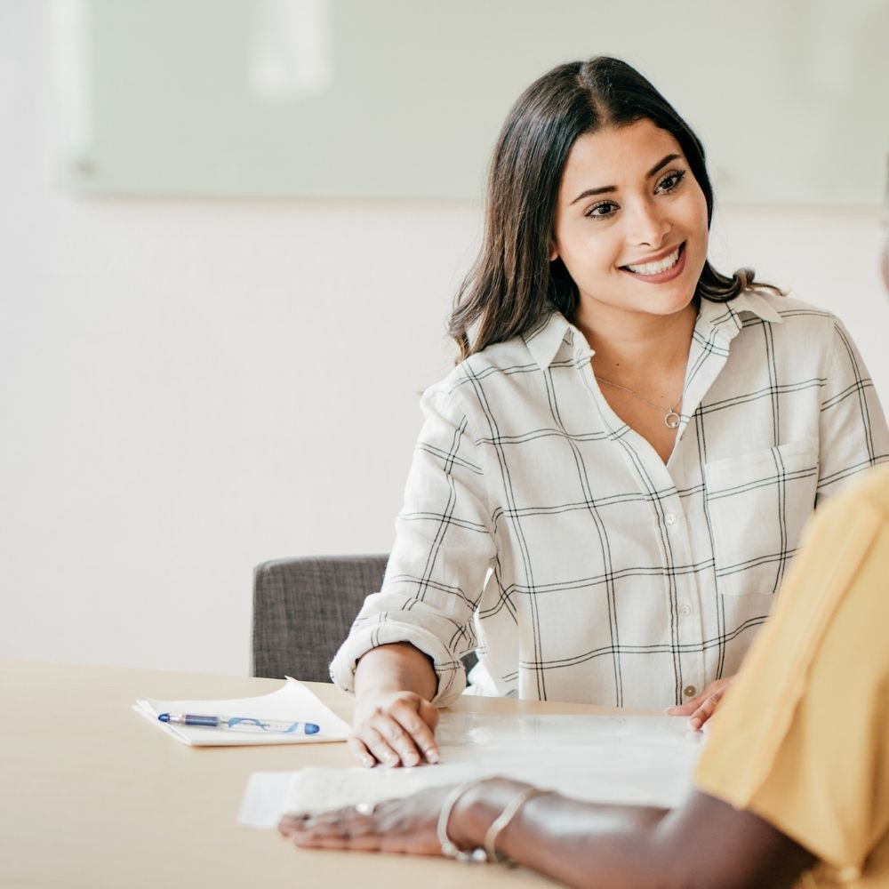 women discussing a resume
